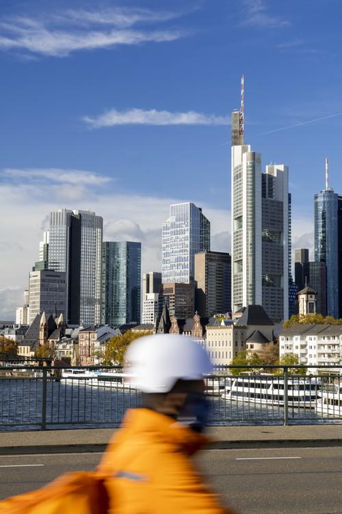 Hochhäuser, Skyline Frankfurt 'Mainhattan', von Alte Brücke. Vermutlich Lieferservice-Fahrer mit Maske. Main. Lieferando, Lieferdienst