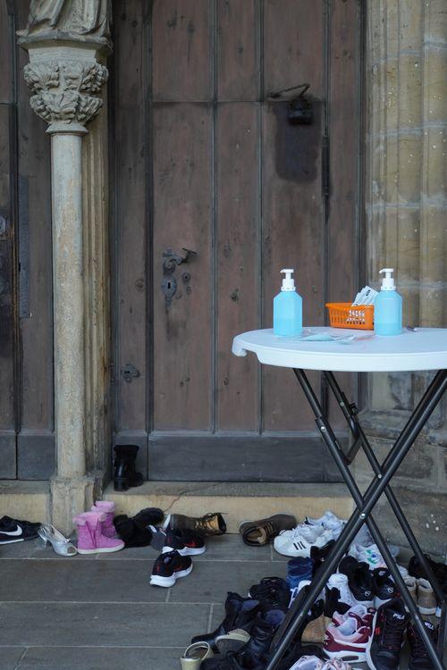 Kirche mit Desinfektionsstand, Registrierung. Schuhe. Tür