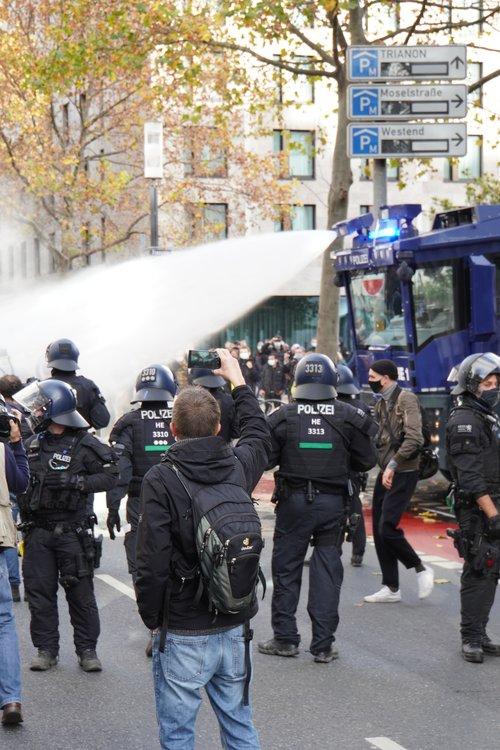Polizei-Wasserwerfer bei Antifa Querdenken-Gegendemo. Handy